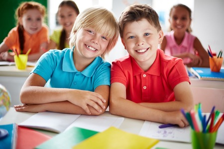 schoolboys: Two cheerful schoolboys looking at camera in classroom