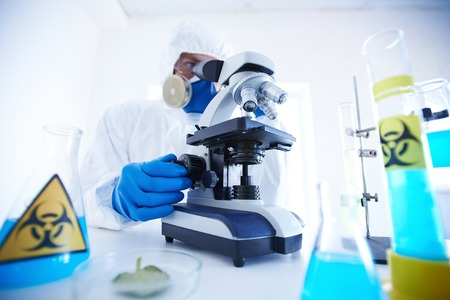 scrutinize: Male scientist in protective clothing working with microscope in laboratory