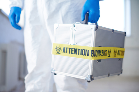 Medical case with biohazard held by gloved scientist