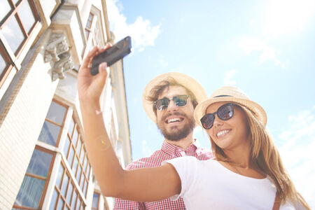 boy romantic: Happy guy and girl in hats and sunglasses making selfie in urban environment