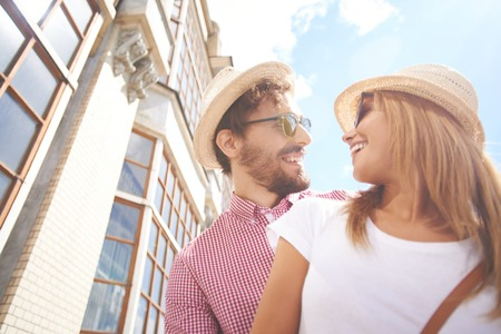 urban environment: Happy couple in hats and sunglasses looking at one another Stock Photo