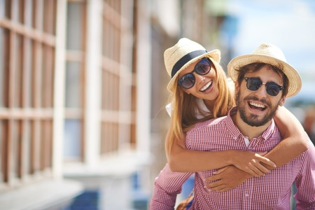 Joyful young dates in hats and sunglasses