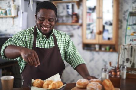 baker: Happy young man powdering buns with vanilla sugar in bakery shop Stock Photo