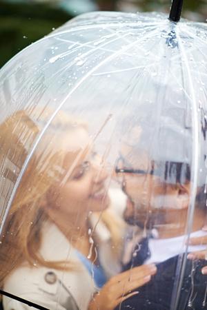 uomo sotto la pioggia: Ritratto di coppia affettuoso sotto l'ombrello guardando l'un l'altro Archivio Fotografico