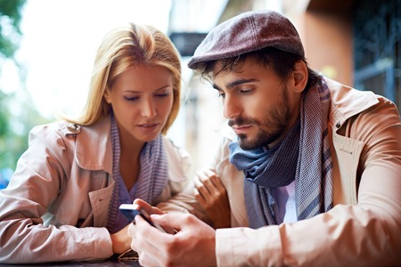 amorous woman: Young couple using cellphone in cafe