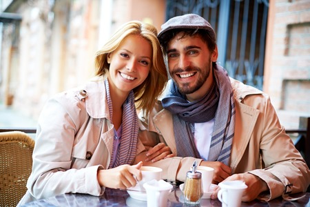 amorous woman: Happy young couple having drink and rest in cafe