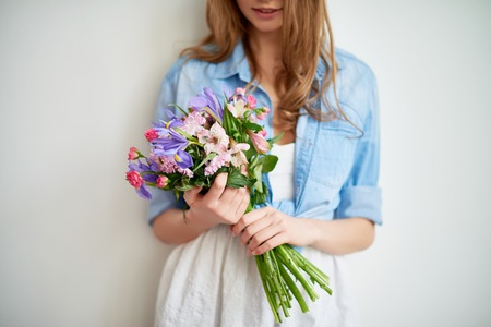 Fresh spring flowers held by a girl in casual