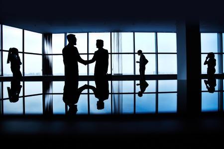 personas saludandose: Siluetas de la gente de negocios en el fondo de la ventana