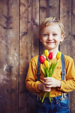 bouquet fleurs: Little boy with bunch of red and yellow tulips looking at camera