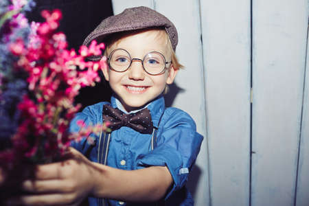 lad: Adorable lad in smart casual and eyeglasses holding wildflowers Stock Photo