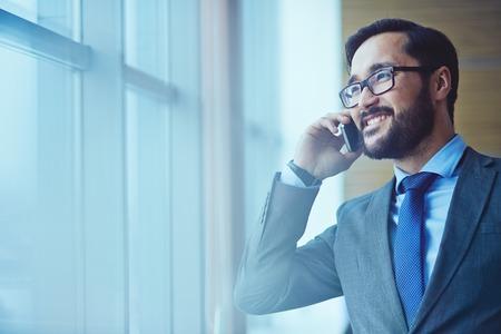 llamando: Sonriente hombre de negocios en gafas hablar por teléfono