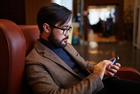 busy beard: Young modern businessman using cellphone