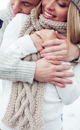 winterwear: Tender man embracing happy girlfriend in winterwear Stock Photo