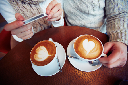romantic love: Two cups of cappuccino on table in cafe and hands of dates