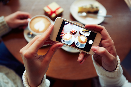 coffees: Two coffees, cheesecake and small giftbox on cellphone display held by one of dates Stock Photo
