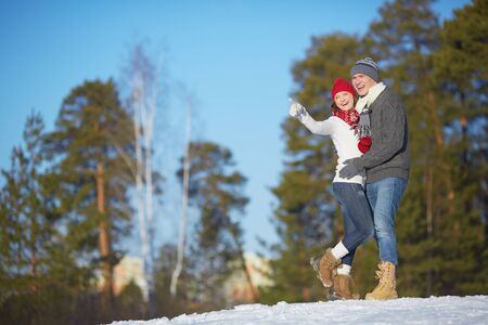 amorous woman: Ecstatic young couple in winterwear spending leisure in park