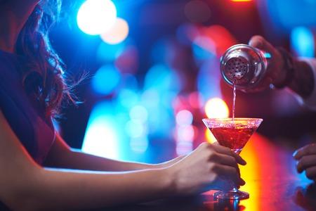Jonge vrouw die martini glas terwijl barman gieten cocktail
