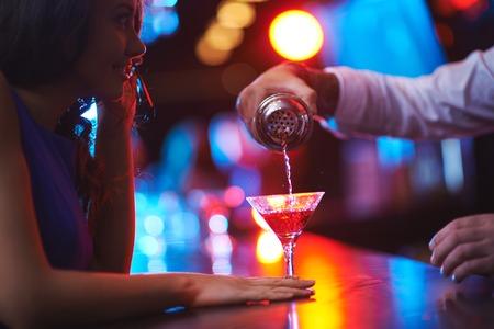 Jonge vrouw te wachten voor haar martini in de bar