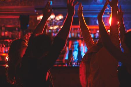 Ecstatic young people enjoying party in nightclub Stok Fotoğraf