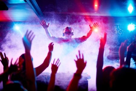 Man deejay in hoofdtelefoons en zonnebril kijken naar dansende menigte