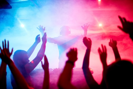 nightclub party: Male deejay in front of dancing crowd