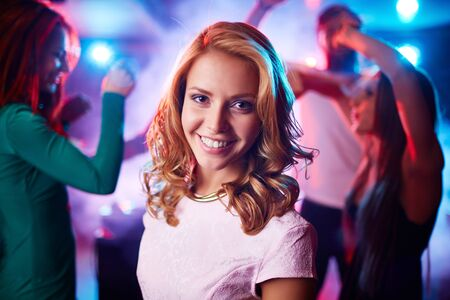 dancing club: Cheerful girl looking at camera on background of dancing friends at party
