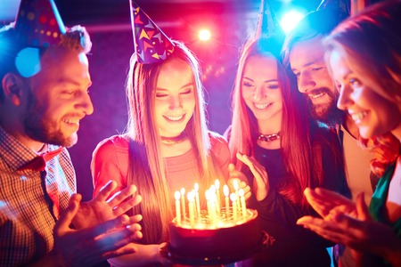 adult birthday: Pretty girl with birthday cake and her friends looking at burning candles at party Stock Photo