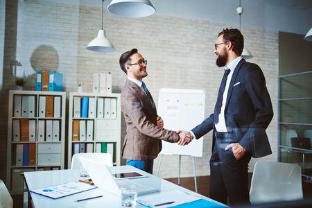 Succesvolle zakenmensen handshaking na onderhandelingen