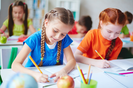 diligent: Diligent girls drawing with crayons at lesson Stock Photo