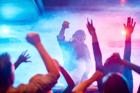 nightclub crowd: Excited deejay encouraging dancing crowd in nightclub