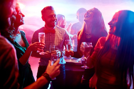 christmas party: Ecstatic friends with champagne talking at party in night club Stock Photo