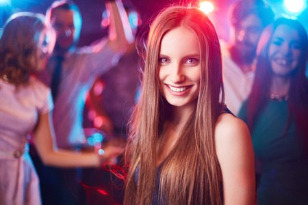 people dancing: Cheerful girl looking at camera on background of her friends dancing