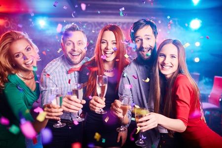 夜のクラブでパーティーを持つシャンパンと酒盛りの友達