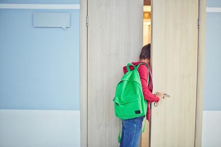 abriendo puerta: Colegial Pre-adolescente tarde a la lección que mira en el aula