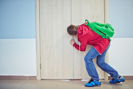 learner: Curious learner with backpack peeping into keyhole of classroom door Stock Photo
