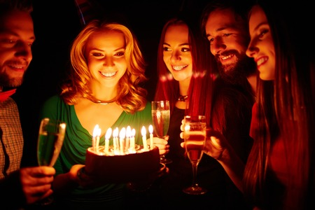 birthday adult: Pretty girl holding birthday cake with burning candles, her friends with champagne surrounding her Stock Photo