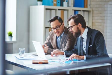 Jonge zakenman met baard toont nieuw project aan zijn collega in het kantoor Stockfoto