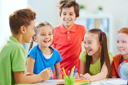 niÑos hablando: Muchachos amistad ya chicas hablando y riendo a la rotura en la escuela Foto de archivo