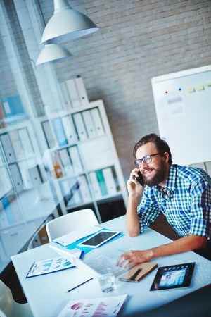 telephony: Happy young businessman speaking on cellphone while working in office Stock Photo
