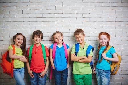 カメラ目線普段着のかわいい学校の友達のグループ