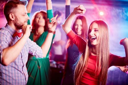 幸せな若いカップルと彼らの友人が一緒に夜のクラブで踊る背景に