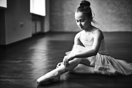 stage costume: Adorable ballerina tying up her shoes Stock Photo