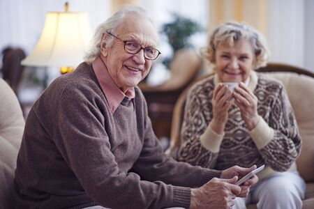 senior home: Senior man with touchpad looking at camera with his wife sitting on background