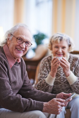 vejez feliz: Hombre mayor con el touchpad mirando a la c�mara mientras descansa en su casa el fin de semana