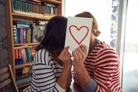 Flirty couple sitting in library behind paper with red heart