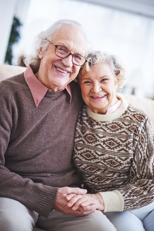 Laughing senior couple in sweaters looking at camera Banque d'images