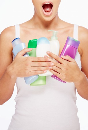 purifying: Amazed woman holding containers with bodycare products