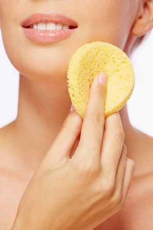 purifying: Young woman with cosmetic sponge removing makeup or applying foundation Stock Photo