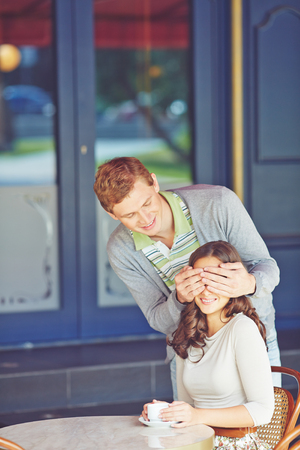 eyes closing: Young man closing his girlfriend�s eyes by hands in cafe