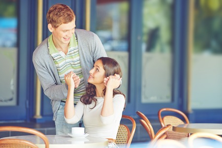 Young woman looking happily at her boyfriend in cafe